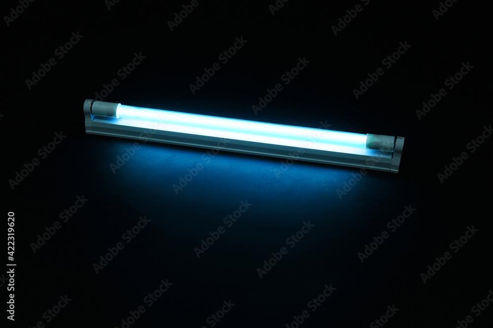 Fototapeta Modern ultraviolet lamp glowing on black background