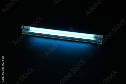 Obraz Modern ultraviolet lamp glowing on black background - fototapety do salonu