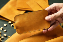 Set Of Handmade Leather Goods In Male Hands, Key Holder Rings, Wallet, Purse, Notepad, Handbook. Handcrafted Leather Goods, Close-up