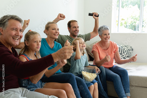 Caucasian parents, grandparents and grandchildren sitting on couch watching tv and cheering