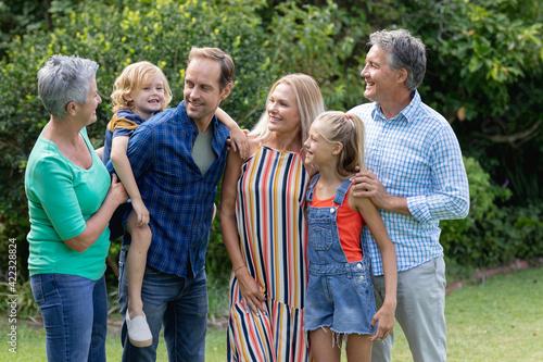 Caucasian parents, grandparents and grandchildren standing in garden talking and embracing