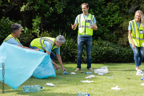 Caucasian multi generation group of men and women collecting rubbish in littered field