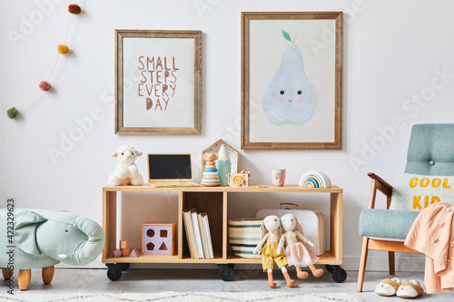 Fotografia Cozy interior of child room with mint armchair, brown mock up poster frame, toys, teddy bear, dolls, plush animal, decoration