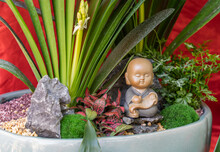 Figure Of Little Monk Beside The Flower Pots