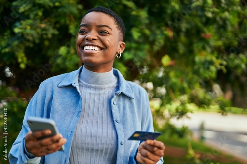Fototapeta Young african american woman smiling happy holding smartphone and credit card at the city obraz