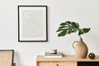 Leinwandbild Motiv Stylish interior of living room with mock up poster frame, wooden commode, book, tropical leaf in ceramic vase and elegant personal accessories. Minimalist concept of home decor. Template.