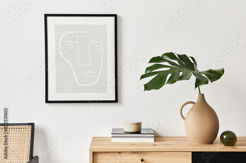 Papel de parede Stylish interior of living room with mock up poster frame, wooden commode, book, tropical leaf in ceramic vase and elegant personal accessories
