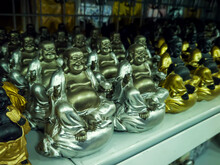Smiling Buddha Statuettes On The Shelf In The Store