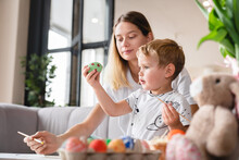 Happy Cute Little Boy Holding Easter Egg With His Mom In The Living Room