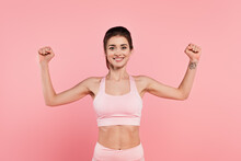 Cheerful Sportswoman Showing Muscles Isolated On Pink