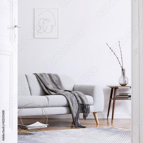 Stylish scandi interior of home space with design grey sofa, ret