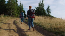 Hikers With Trekking Poles Walking On Road. Man And Woman Wearing Backpacks