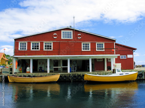 Foto Small fishing craft in Norway, two yellow boats in front of a Falun red boathouse