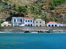 Waterfront Homes On A Tropical Island, Brava Island, Cabo Verde, Blue Ocean Water, Stony Beach And Terraced Fields On The Hills.