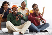 Joyful African American Friends Playing Video Games At Home