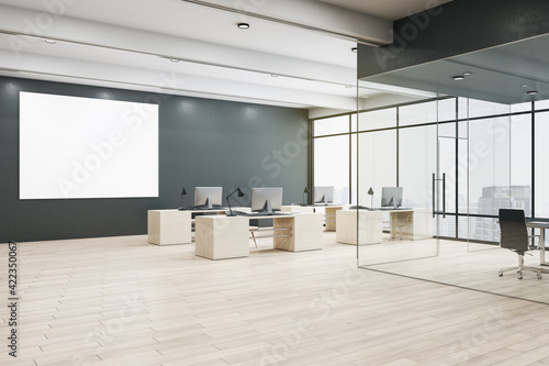 Fototapeta Blank white poster on black wall in spacious office hall with modern eco furniture, wooden floor and meeting room with glass walls. Mockup obraz