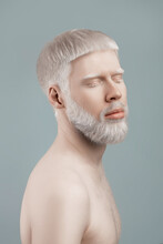 Calm Albino Bearded Guy With Closed Eyes Posing Against Grey Background In Studio