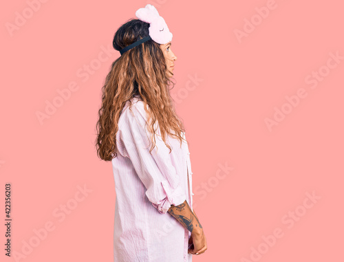 Young hispanic woman with tattoo wearing sleep mask and pajama looking to side, relax profile pose with natural face with confident smile.
