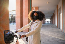 Portrait Young Commuter Woman In City Sustainable Way With Bike Wearing Protective Face Mask Against Coronavirus Covid-19 Pandemic Rides Bicycle On Way Home To Work Safety And Commuting Concept