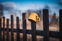 Yellow Mug On A Wooden Fence Close Up. Blue Sky In Background.
