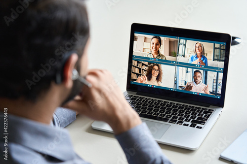 Fototapeta Indian business man wearing headset having virtual team meeting on video conference call using laptop work from home office talking to diverse group in remote online distance chat. Over shoulder view obraz