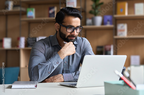 Obraz na plátně Young serious indian professional business man, focused ethnic male student wearing glasses working on laptop, remote studying using computer looking at screen watching seminar webinar at home office