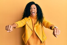 Middle Age African American Woman Doing Motorcycle Symbol With Hands Celebrating Crazy And Amazed For Success With Open Eyes Screaming Excited.