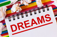 On A Multi-colored Striped Background There Are White Pieces Of Paper And A White Notebook With The Inscription In Red DREAMS
