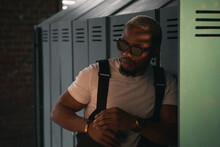 Stylish Glamor Handsome African Man With White Short Hair Wearing White T-shitr, Black Pants And Sunglasses Standing And Leaning On Boxes In Gym