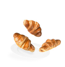 Levitation Of Three Croissants On A White Plate And White Background.