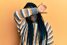 Young Black Woman With Braids Wearing Casual Winter Sweater Covering Eyes With Arm, Looking Serious And Sad. Sightless, Hiding And Rejection Concept