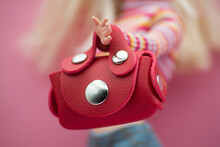 Closeup Of Mini Red Leather Bag In Hand Of Blond Mannequin Doll  On Pink Background