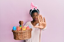 Young African American Girl Wearing Cute Easter Bunny Ears Holding Basket With Painted Eggs With Open Hand Doing Stop Sign With Serious And Confident Expression, Defense Gesture