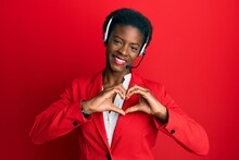 Young African American Girl Wearing Call Center Agent Headset Smiling In Love Showing Heart Symbol And Shape With Hands. Romantic Concept.