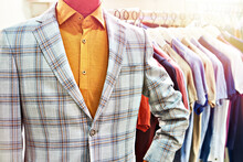 Men's Plaid Blazer Jacket On A Mannequin And Shirts On Hangers
