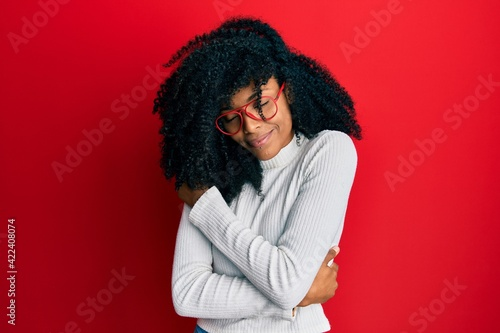 Canvas-taulu African american woman with afro hair wearing casual sweater and glasses hugging oneself happy and positive, smiling confident