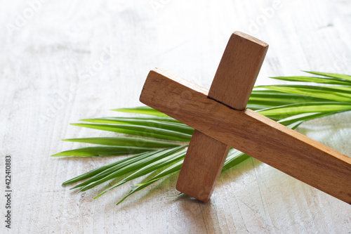 Wooden cross and palm on light background, palm sunday concept