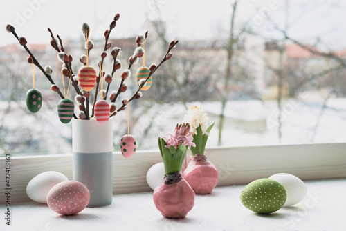 Obraz Easter decorations on windowsill, panoramic image. Wooden painted eggs on pussy willow. Hyacinth flowers with bulbs in pink wax. Window, view over town. Romantic indoor setup. Happy Easter - fototapety do salonu