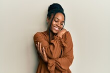 African American Woman With Braided Hair Wearing Casual Brown Shirt Hugging Oneself Happy And Positive, Smiling Confident. Self Love And Self Care