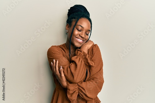 Canvastavla African american woman with braided hair wearing casual brown shirt hugging oneself happy and positive, smiling confident