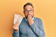 Handsome Middle Age Man Holding 10 United Kingdom Pounds Banknotes Covering Mouth With Hand, Shocked And Afraid For Mistake. Surprised Expression