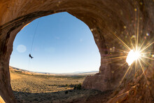 A Woman Rappelling Into The Looking Glass Arch, La Sal, Utah.