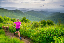 A Woman And Her Dog Trail Running Along The Art Loeb Trail Over Black Balsam Knob, Pisgah National Forest, Brevard, North Carolina.