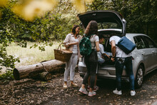 Family Removing Things From Car Trunk In Forest During Picnic