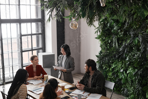 Fototapeta High angle portrait of diverse group of business people meeting at table in modern office interior decorated by plants, copy space obraz