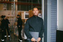 Confident Male Entrepreneur Standing With Clipboard At Logistics Warehouse