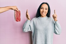 Young Hispanic Girl On Diet Rejecting Beef Smiling With An Idea Or Question Pointing Finger With Happy Face, Number One