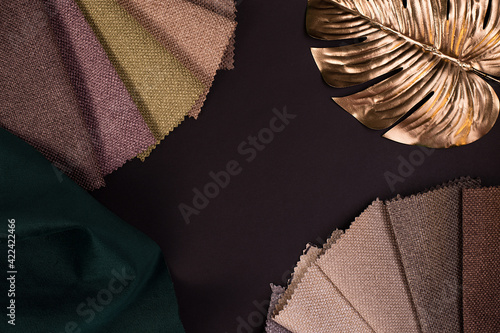 Fototapeta Light Set Sail Champagne and grey colors gunny textile samples decorated with gold monstera leaves on a black table. obraz