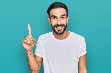 Young hispanic man wearing casual white t shirt showing and pointing up with finger number one while smiling confident and happy.