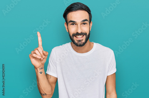 Fototapeta Young hispanic man wearing casual white t shirt showing and pointing up with finger number one while smiling confident and happy. obraz